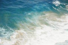 Blaues Wasser mit Schaumgummi am Ozeanufer lizenzfreie stockbilder