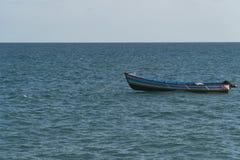 Blaues Wasser und alleinboot Stockfotos