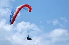 Blaues, weißes und rotes Gleitschirmfliegen Lizenzfreie Stockfotos