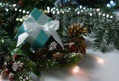 Blaues Weihnachtsgeschenk angeschmiegt in den Dekorationen Stockbilder