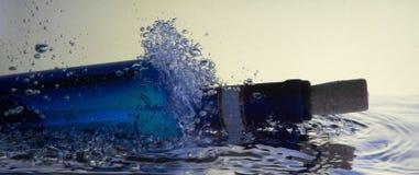 Blaues Weinflaschenspritzen stockfotografie