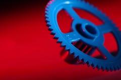 Blaues Zahnrad auf einem roten Hintergrund Lizenzfreie Stockbilder