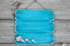 Blaues Zeichen der leeren Knickente mit den Muscheln, die an der rustikalen Holztür hängen Stockfotos