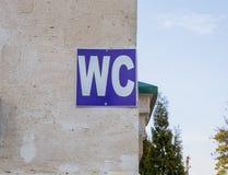 Blaues Zeichen von WC der öffentlichen Toiletten auf einer Steinwand Lizenzfreies Stockfoto