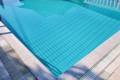 Blaues zerrissenes Wasser im Swimmingpool im tropischen Erholungsort mit Rand der Pflasterung Teil unterer Hintergrund des Swimmi stockfotografie