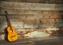 Blaugitarre die alte hölzerne Wand als Hintergrund Stockfotografie