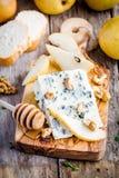Blauschimmelkäse mit Scheiben der Birne und des Honigs Stockfotografie