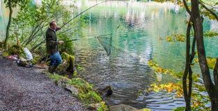 Blausee, Switerland -钓鱼者和鳟鱼 免版税库存图片