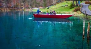 Blausee, Suiza - visitando puntos de interés en barcos rojos Fotografía de archivo libre de regalías