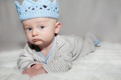 Blauäugiges Baby, das blaue Knit-Krone trägt Stockbild