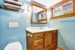 Blauw badkamersbinnenland met houten ijdelheidskabinet Stock Foto