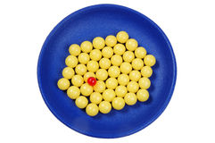 Blauw bordvol van gele dalingenvitamine en rode pil Royalty-vrije Stock Foto's