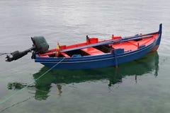 Blauw die houten die boot vissen in het overzees wordt vastgelegd royalty-vrije stock afbeeldingen
