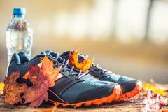 Blauw die sportschoenen en water op een houten raad worden gelegd stock foto