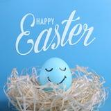 Blauw ei met geschilderde glimlachen in het nest, exemplaarruimte Gelukkig Pasen-de kaartontwerp van de conceptengroet royalty-vrije stock fotografie