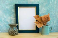 Blauw en gouden kadermodel, concrete muurachtergrond, houten lijst, gebraden gerechtbladeren, de lamp van de aromatherapie, de he stock afbeelding