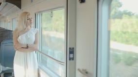 Blauw-eyed blonde die zich door het venster van de trein bevinden stock videobeelden