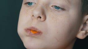 Blauw-eyed, freckled tienerjongen die chips eten die als grote leervoorzitter zitten stock video