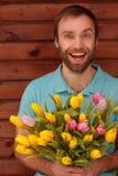 Blauw-eyed gebaarde mens met bloemen op houten achtergrond Stock Foto's
