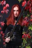 Blauw Eyed Rood Hoofd Gotisch Meisje die een fantasiezwaard onder de herfstwijnstokken houden stock fotografie