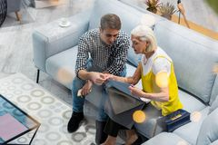 Blauw-gespoeld mevrouw die gesprek met zoon hebben die laag het textiel selecteren overeenstemmen stock foto's