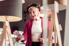 Blauw-gespoelde charmante bejaarde dame die smilingly verkoopteken bekijken stock foto