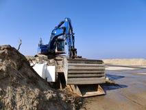 Blauw graafwerktuig op stapel van zand op bouwwerf Stock Foto's