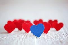 Blauw hart en vele rode harten op de witte achtergrond valentin Stock Afbeeldingen