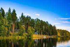 Blauw houten saunablokhuis op het meer in Finland Stock Afbeelding