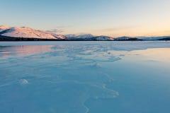 Blauw ijs van het bevroren meer bij ochtend De winterlandschap in de bergen en de de winterweg in Yakutia, Siberië, Rusland stock foto's