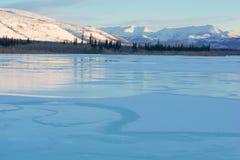 Blauw ijs van het bevroren meer bij ochtend De winterlandschap in de bergen en de de winterweg in Yakutia, Siberië, Rusland stock afbeeldingen