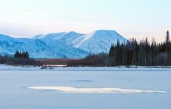 Blauw ijs van het bevroren meer bij ochtend De winterlandschap op de bergen en het bevroren meer in Yakutia, Siberië, Rusland royalty-vrije stock afbeeldingen