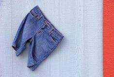 Blauw Jean Capri Shorts op blauwe grijze muur rode grens Stock Fotografie