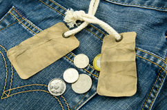 Blauw Jean met leeg prijskaartje en muntstukken op achtergrond Stock Fotografie