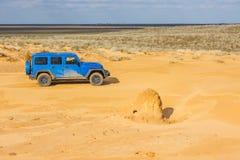 Blauw Jeep Wrangler Rubicon Unlimited bij de duinen van het woestijnzand Stock Foto's