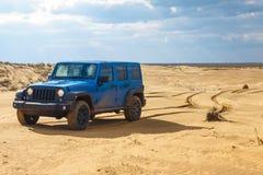 Blauw Jeep Wrangler Rubicon Unlimited bij de duinen van het woestijnzand Stock Fotografie
