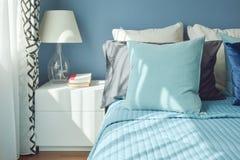 Blauw kleurenschemabeddegoed en witte schemerlamp met natuurlijk licht Royalty-vrije Stock Afbeelding