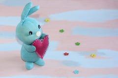 Blauw leuk konijntje met een rood hart in zijn poten op een roze lichtblauwe achtergrond Handwork royalty-vrije stock foto's