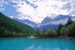 Blauw meer bij de voet van sneeuwberg stock foto's