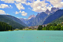 Blauw meer met stegen onder een blauwe hemel met witte wolken in bergen Royalty-vrije Stock Foto's
