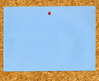 Blauw notadocument dat aan cork wordt geplakt noticeboard. royalty-vrije stock afbeeldingen
