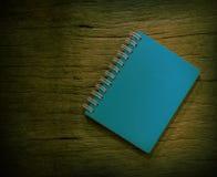 Blauw notitieboekje met uitstekende achtergrond van oud hout Royalty-vrije Stock Afbeeldingen