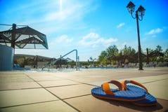 Blauw pantoffels dichtbij zwembad bij poolside Royalty-vrije Stock Foto's