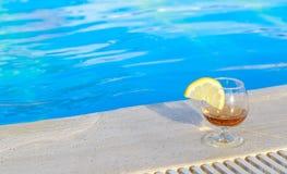 Blauw poolwater, een glas op smaak gebrachte cognac met een plak van citroen bij de water` s rand royalty-vrije stock afbeeldingen