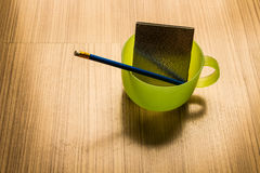 Blauw potlood en notitieboekje in een kop van groen water Royalty-vrije Stock Foto
