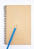 Blauw potlood op de dekking van het bruine notitieboekje. Royalty-vrije Stock Afbeeldingen