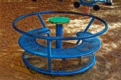 Blauw roestig speelplaatsspinnewiel Stock Foto's