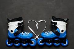Blauw rolschaatsen en hart van kant op donkere schoolbordachtergrond De dag van de valentijnskaart `s Stock Fotografie