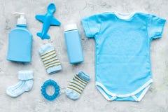 Blauw voor pasgeboren jongen wordt geplaatst die Babybodysuit, sokken, airplan stuk speelgoed, zeep en poeder op grijze hoogste m royalty-vrije stock afbeeldingen