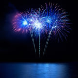 Blauw vuurwerk hierboven - water Stock Afbeelding